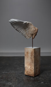 Contemporary art work - Sculpture by Maya Kulenovic. WING / SAND (Var. #2), 2021, polymerized concrete blend, sand, iron oxide, iron. Realistic sculpture of a wing, damaged as if by erosion to expose sand/clay material under pristine white surface.